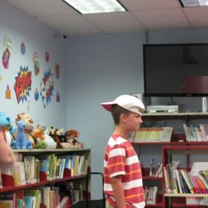 Valerie using a yo-yo to know a hat off Seth's head